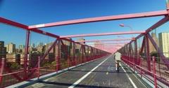 Following a Biker on Pedestrian Sidewalk on Williamsburg Bridge Stock Footage