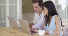 Couple working on laptop computers together Stock Footage