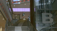 Young woman walks downstairs in mall Stock Footage