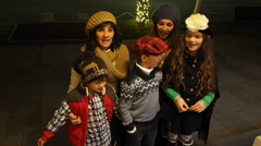 Family singing christmas carols on front porch at night Stock Footage