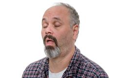 Balding man with beard and plaid shirt snores Stock Photos