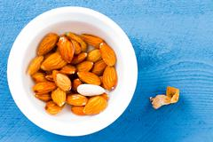 Bowl of fresh raw almonds with one peeled Stock Photos