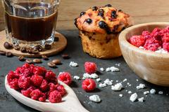 Curd with raspberries, coffee in a cup and blueberry muffin for breakfast Stock Photos