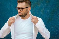Fashion man with glasses adjusts his white jacket Stock Photos