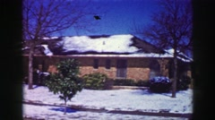 1969: Suburban snow covered brick ranch style house melting winter blizzard. Stock Footage
