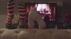Little feet kicking on couch with fireplace on tv in background 4k Stock Footage