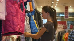 Mother buys clothes for a baby Stock Footage