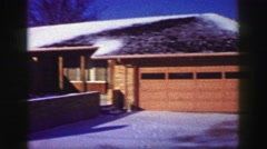 1969: Suburban closeup snow covered brick ranch style house melting winter Stock Footage