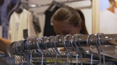 Young woman chooses clothing in store Stock Footage
