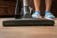 Woman with vacuum cleaner cleaning wooden laminate floor at home Stock Photos