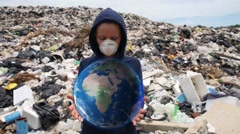 Woman in Mask Holding Hologram Planet Earth at Landfill Site Stock Footage