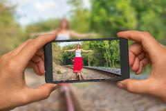 Woman hands with mobile cell phone to take a photo of young lady in red dress Stock Photos