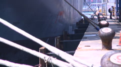 Cargo ship docked in port. The container ship is tied to bollards. Stock Footage
