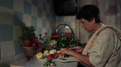 Mature woman prepares vegetables for preservation in the kitchen. Stock Footage