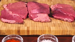 Man fights off raw meat beef steak before frying it slow motion Stock Footage