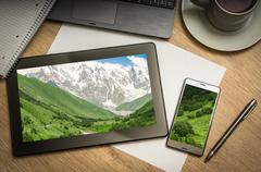 Digital tablet on business table with snow-capped mountains in Georgia on scr Stock Photos