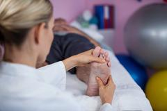 Physiotherapist giving foot massage to a patient Stock Photos