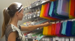 Schoolgirl chooses book covers in stationery store Stock Footage