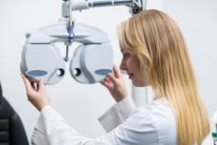 Attentive female optometrist adjusting phoropter Stock Photos