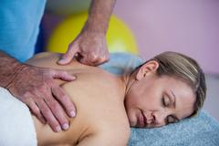 Woman receiving back massage from physiotherapist Stock Photos