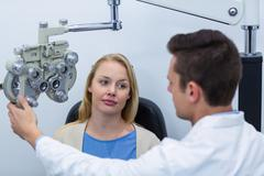 Optometrist interacting with female patient Stock Photos