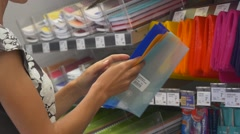 Young woman chooses book covers in stationery Stock Footage