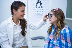Female optometrist examining young patient with trial frame Stock Photos