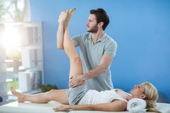 Male physiotherapist giving knee massage to female patient Stock Photos