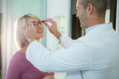 Optometrist consulting a customer about spectacles and frames Stock Photos