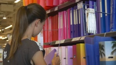Woman chooses a folder in stationery Stock Footage