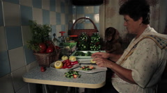 Mature woman prepares vegetables for preserving and communicating with the dog d Stock Footage