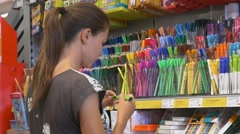 Girl chooses among different colors of highliters Stock Footage