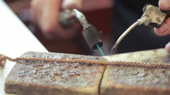 a jeweler behind a desk solder product. repair gold chain - stock footage