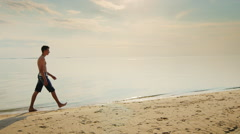 Teenager boy walking along the beach at sunset. Against the backdrop of the Stock Footage