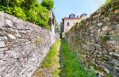 Landscape with narrow street with stone walls of the Maccagno, Italy Stock Photos