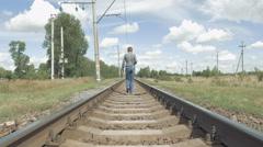 Woman walks along railway tracks in countryside Stock Footage