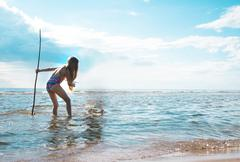 Girl with a trident in his hand looks at the sea surface Stock Photos