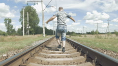 Smiling man jumping dancing on the railway tracks Stock Footage