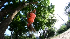 Girl on a rope swing hanging upside down. Stock Footage