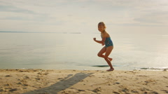 Carefree blonde girl 5 years runs along the shore. He laughs off her feet flying Stock Footage