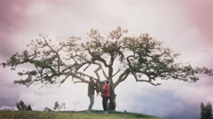 Couple with dog under ancient tree Stock Footage