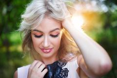 Beautiful young woman posing in a summer park Stock Photos