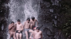 Group of boys together under cascade Stock Footage