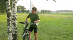 A young man cyclist stops and drink water from bottle. Against the background of Stock Footage