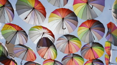 Decoration with hanging umbrellas coloring the sky over city street Stock Footage