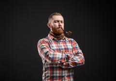 Elegant bearded man holding smoking pipe Stock Photos