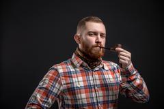 Elegant bearded man holding smoking pipe Stock Photos