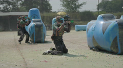 Paintballplayer on the Field while a Battle is going on in 4K Stock Footage