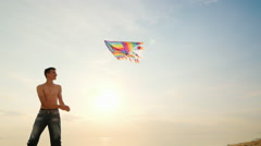Boy teenager playing with a kite. Against the background of blue sky, side view Stock Footage