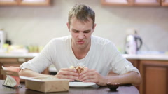 Handsome man chewing and enjoying a hamburger with fries at home Stock Footage